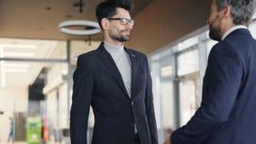 Sócios comerciais na reunião do formalwear no café que agita as mãos e a fala vídeos de arquivo