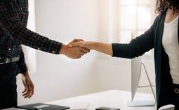 Sócios comerciais que agitam as mãos em uma reunião imagens de stock royalty free