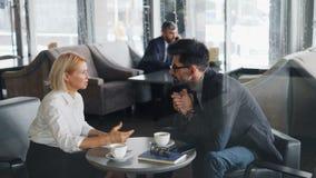 Sócios comerciais que discutem a cooperação no café que fala durante a pausa para o almoço video estoque