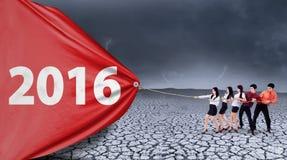 Sócios comerciais que puxam os números 2016 com uma bandeira Imagem de Stock Royalty Free