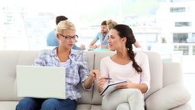 Sócios criativos que compartilham de ideias no sofá com os colegas atrás video estoque
