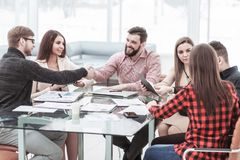 Sócios financeiros do aperto de mão após o exame de um contrato novo imagens de stock royalty free