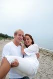 Sócios novos que têm o divertimento pela praia Imagem de Stock Royalty Free
