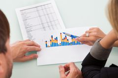 Sócios que discutem um gráfico de negócio Imagem de Stock Royalty Free