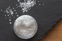 Sól w zbiorniku z solankowymi płatkami na czerń łupku tle na drewnianym stole zdjęcia stock