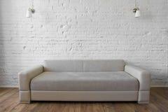 Sótão bege do sofá do assoalho de madeira branco da parede de tijolo Fotografia de Stock