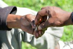 Södra - afrikanhänder som utbyter cigaretten Royaltyfri Foto