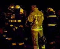 Södra - afrikanska brandmän i bunkerkugghjul på natten Royaltyfri Bild