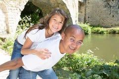 Södra - amerikansk fader Giving Daughter Ride på ryggen på skuldror royaltyfria foton