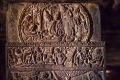 Södra indiskt folk och liv i forntida byar, sniden vägg inom de 7th århundradetemplen i Pattadakal, Indien Arkivfoto