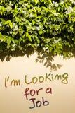 Söka efter ett jobb som är skriftligt på en murbrukvägg arkivbild