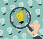 Sökande för idé - lightbulbs och hand med förstoringsapparaten Royaltyfria Foton