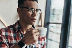 Sökande för inspiration Stilig ung man dricka kaffe arkivbild