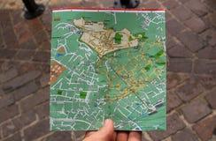 Sökande för riktningar på en stadsöversikt med handen Arkivfoto
