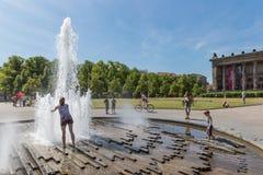 Sökande uppfriskning för okänt folk på en varm sommardag på plazaen nära BerlinerDom Fotografering för Bildbyråer