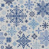 Sömlös stucken modell med blåa snöflingor på en vit backgro Royaltyfria Bilder