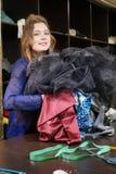 Sömmerska, costumier eller säljare som rymmer en grupp av klänningar Stående av kvinnan i studio royaltyfria foton