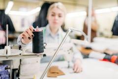 Sömmerskahänder syr tyger på en symaskin royaltyfria bilder