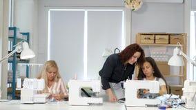Sömmerskaläraren undervisar hennes studenter att sy på symaskiner i seminarium arkivfilmer