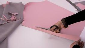 Sömmerskan klipper rosa tyg med sax för att sy en tröja Bitande tyg arkivfilmer