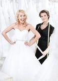 Sömmerskan korrigerar klänningen av bruden Royaltyfria Bilder