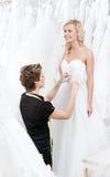 Sömmerskan mäter midjan av bruden fotografering för bildbyråer