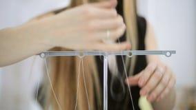 Sömmerskan som in fyller trådsergeren för att bearbeta silkespappret, kantar lager videofilmer