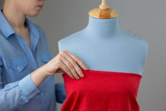 Sömmerskan som mäter härligt tyg på blått, anpassar attrappen i hennes seminarium Royaltyfri Fotografi