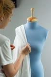 Sömmerskan som mäter härligt tyg på blått, anpassar attrappen i hennes seminarium Royaltyfria Bilder