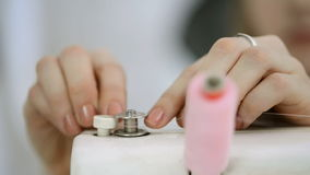 Sömmerskan spolar tillbaka tråden på spolen på symaskinen lager videofilmer