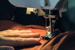 Sömmerskan syr kläder som göras av den röda torkduken på en symaskin Arkivfoto