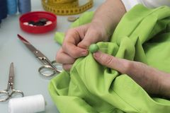 Sömmerskan syr knappen till en grön skjorta Royaltyfri Fotografi