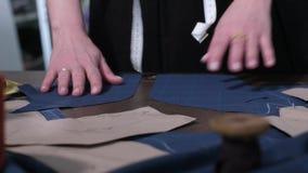 Sömmerskas händer som lägger den ut klippta modellen på tabellen lager videofilmer