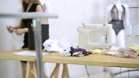 Sömmerskasnitt dragar från snör åt tyg på symaskiner i atelier stock video
