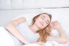 sömn Ung kvinna som sover i säng, stående av den härliga kvinnlign som vilar på bekväm säng med kuddar i vit sängkläder royaltyfri fotografi