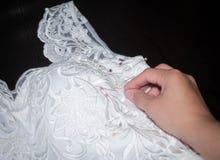 Sömnadbröllopsklänning, handsömmerska som rymmer en visare över tygmodellen Arkivfoto