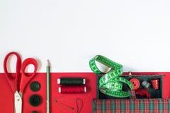 Sömnadtillbehör i röda och gröna färger Arkivbild