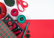 Sömnadtillbehör i röda och gröna färger Arkivfoto