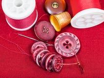 Sömnadtråd, knappar, fingerborg på den röda textilen Arkivbilder