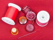 Sömnadtråd, knappar, fingerborg på rött silkespapper Royaltyfria Foton