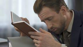 Sömnig överansträngd kontorsarbetare som försöker att läsa rapporten på arbetsplatsen, övertid arkivfilmer