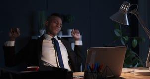 Sömnig affärsman som sträcker och använder bärbara datorn på nattkontoret stock video