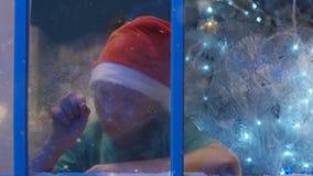 Sömnig drömma pojke som ser i fönster i jultid stock video