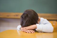 Sömnig elev som ta sig en tupplur på skrivbordet i klassrum Royaltyfria Bilder