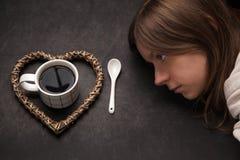 Sömnig flicka som ser på en kopp av svart kaffe Royaltyfri Bild