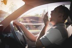 Sömnig gäspa man som kör bilen i trafik efter drev för lång timme Fotografering för Bildbyråer