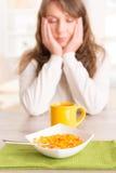 Sömnig kvinna som hemma äter frukosten arkivfoton