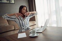 Sömnig kvinna som hemma arbetar med en bärbar dator som en freelancer fotografering för bildbyråer