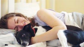 Sömnig le kvinna och hennes hund i sängen HD lager videofilmer