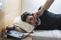 Sömnig man på säng som gäspar, medan tala på Arkivbild
